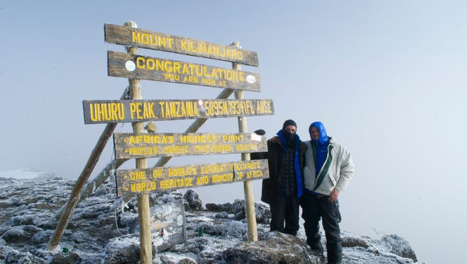 Jeff Crider and his son Max celebrate their successful climb to the summit of 19,341-foot Mount Kilimanjaro.