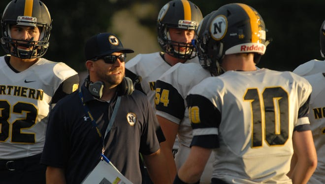 Huskies head coach Larry Roelens talks with quarterback Billy Fealko during a Port Huron Northern football game.