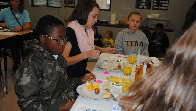 """Xavier Mason and Evelyn Finney were among the lucky few to draw an upper-income ticket at the """"hunger banquet"""" their class organized at Thurman Francis Arts Academy."""