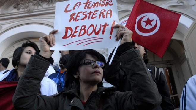 """A Tunisian woman holds a placard reading in French """"Tunisia will remain standing"""" as she takes part in a protest on March 18, 2015 after an attack on the National Bardo Museum in Tunis. Tunisia's president promised to wage """"war against terrorism"""" after gunmen killed at least 17 foreign tourists and two Tunisians in a daylight attack in the birthplace of the Arab Spring."""