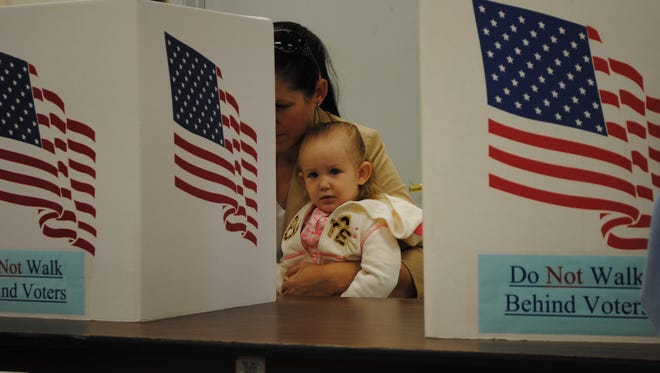 A future voter doesn't look impressed by any of the choices Tuesday morning, Nov. 8, at the Middle Amana Fire Station.