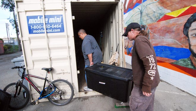 A participant in the Street Lights program, right, gets some help putting his possessions into the trailer next to the Chinatown Learning Center on Tuesday, April 25th, 2017.