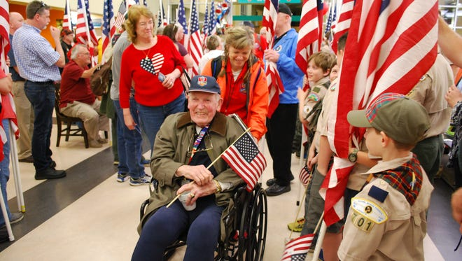 Frank E. Blazey, a retired Army general who served in Korea and Vietnam, makes his way through the terminal at Asheville Regional Airport on Saturday night. He traveled to Washington as part of the Blue Ridge Honor Flight.