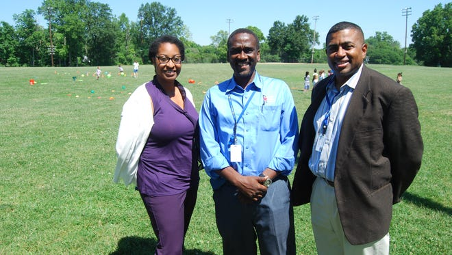 Tiffany Stewart, Daniel Betts and Lathel Bryant with the Cincinnati Recreation Commission are preparing for the commission's 90th anniversary party July 8. They are standing in the athletic field at the Oakley Recreation Center, where the event will take place.