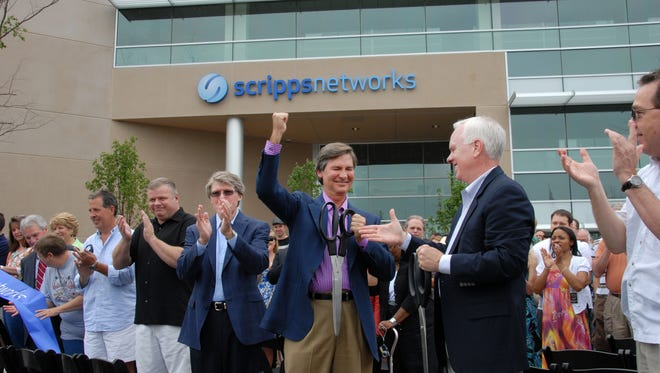 Scripps Networks Interactive CEO Ken Lowe, center; Mark Hale, senior vice president of technology operations and chief technology operator at Scripps Networks Interactive, at left; and Scripps Networks President John Lansing, at right, along with Scripps employees and community dignitaries participate in a ribbon-cutting ceremony Saturday, May 15, 2010, for the 150,000-square-foot expansion at its headquarters in West Knoxville.