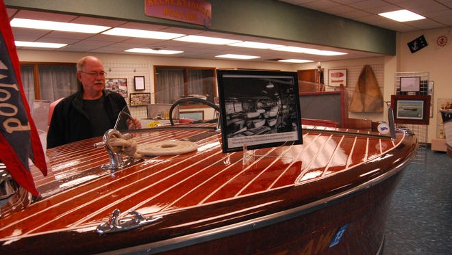 Terry Wallis with an antique wooden boat at the Algonac-Clay Township Historical Society's maritime museum