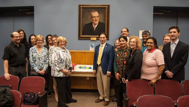 East Brunswick Mayor Brad J. Cohen (center right) joins East Brunswick Public Library staff, as well as members of the Board of Trustees, Friends of the Library, Library Foundation and township council members in celebrating the library's 50th anniversary at the April 3 council meeting.