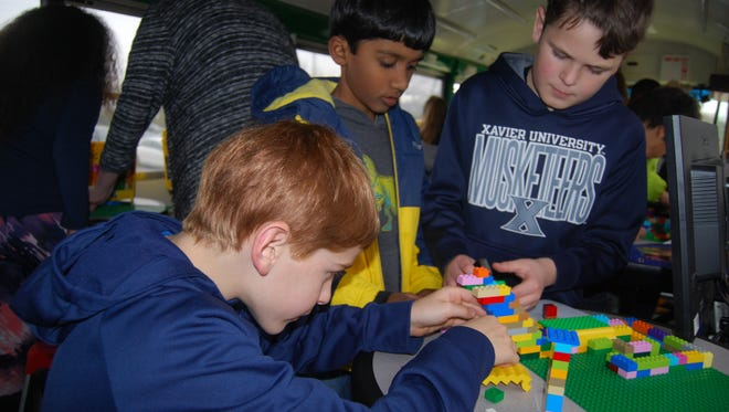 Blue Ash Elementary School third-graders Owen Carr, left, Arya Gandhapudi and Barrett Burden work on building a Lego maze inside of a bus retrofitted for science and math activities. Dec. 5, 2017