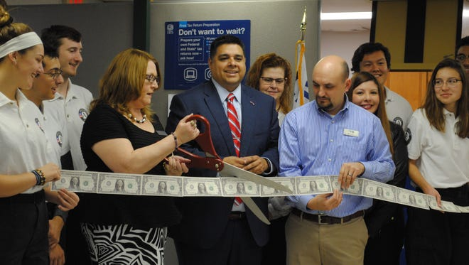 VITA Coordinator Genevieve Anderson cuts a money ribbon Friday during an opening ceremony at the Wichita Falls office. VITA offers free tax preparation for moderate to low income tax payers.