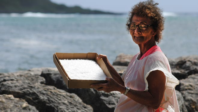 Rose San Nicolas, 72, is a cultural craftswoman and master weaver of shrimp traps. She is shown here with a tray of salt that has been harvested, then dried and bleached in the sun for several days. Behind her is Inarajan bay, where she collected the seawater that she boiled to harvest the salt crystals left behind.