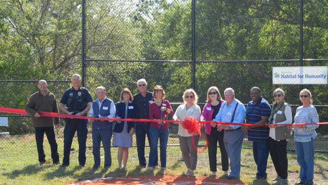 Meadows Field ribbon cutting ceremony at Habitat's Grace Meadows Community in Fellsmere. From left to right: Mark Mathes, Keith Touchberry, Stephen Anderson, Patricia Brier, Andy Bowler, Connie Poppell, Susan Adams, Bernadette Emerick, Joel Tyson, Anthony Brown, Suzanne Carter and Diana Mancini.
