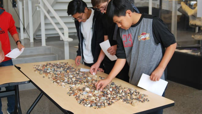 Kirtland Middle School eighth-graders Terrence Washburn, Mathew Shelby and Jakari McDonald examine rock samples during Energy Week on May 7 at San Juan College.