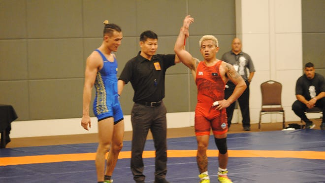 Ethan Aguigui, right, is declared the winner and gold medalist after his victory over Palau's Cristian Nocolescu during the Oceania Wrestling Championships 65kg senior class division May 18 at the LeoPalace Resort.