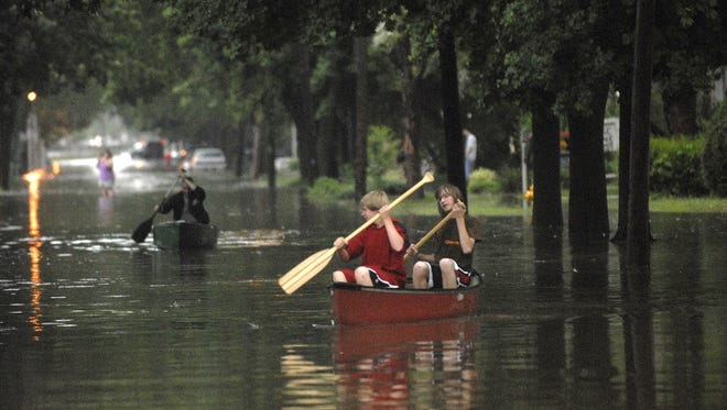 Alek Glish, left, and Zach Rockow canoe down Gillett Street during a lull in the 2008 storm that flooded much of Fond du Lac.