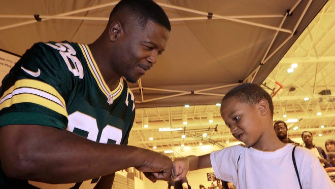 Leroy Butler  greets Jmari Williams, 6, from Milwaukee during the Milwaukee Health Department's Back-to-School Health Fair at North Division High School on Aug. 7, 2015.