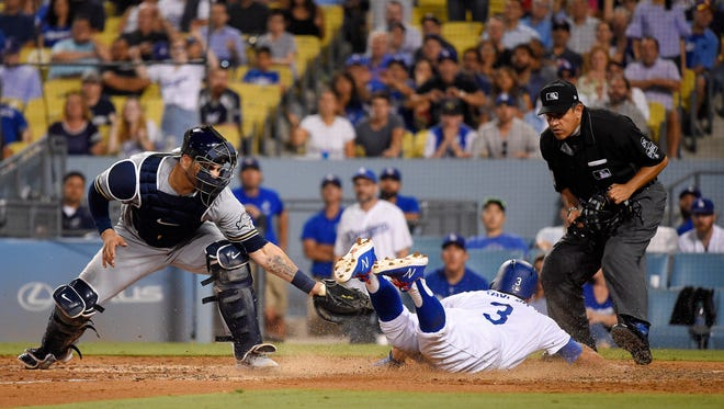 Chris Taylor slides past Brewers catcher Manny Pina as he scores on a squeeze bunt during a regular-season game.