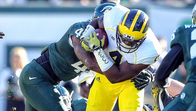 Michigan running back De'Veon Smith, right, gets tackled by Michigan State in 2014.