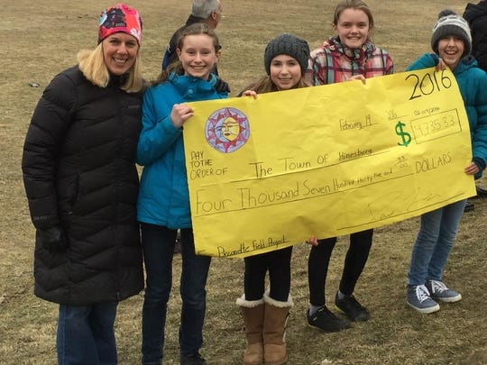 Jen McCuin, Hinesburg Recreation director, accepting a check from sixth-grade students, from left, Phoebe Dennison, Caille Comeau, Chloe Stidsen and Lizzy Charney.