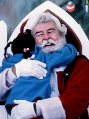 Santa Claus gets an enthusiastic hug from 6-year-old
