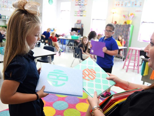 First-grader Palyn Brock, 5, grabs a folder from teacher