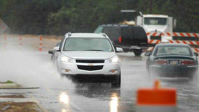 Motorists driving along Hoy Road near U.S. 51 in Madison splash through water standing on the roadway as rain spawned by Tropical Storm Lee sweeps across the metro area on Sunday.