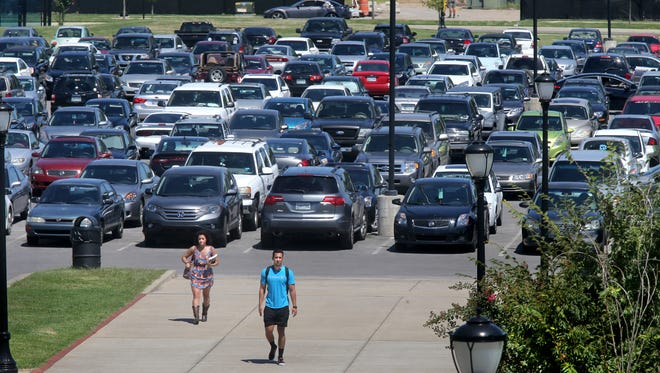 People walk from the Greenhouse Lot as cars circle the parking lot tring to find a space, on Wednesday, Aug. 26, 2015.  MTSU soon will charge visitors a $2 fee to park on campus a day.
