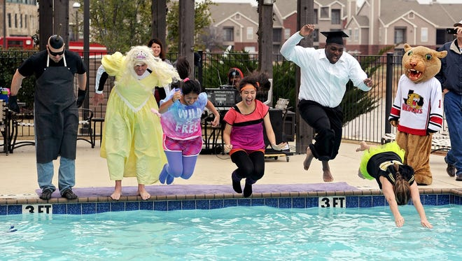 A group from Rider High School jumps into the pool at the Holiday Inn Express during the Seventh Annual Polar Plunge in 2015.