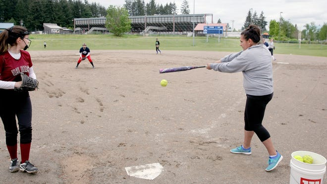 Olympic High School softball coach Jessica Cabato hits infield in practice.