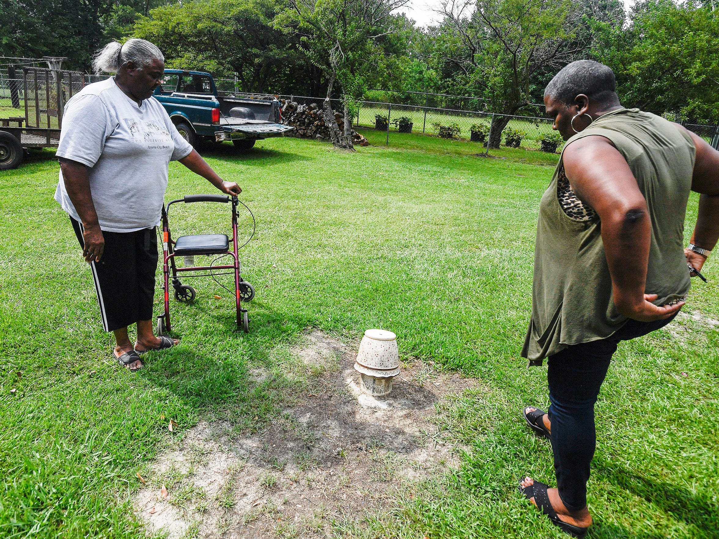 Charlie Mae Holcombe, left, and Mary McDonald stand by the cover to Holcombe's septic tank at her home in Hayneville, Ala. on Friday July 6, 2018. Holcombe has had decades of flooding and sewer problems at her home.