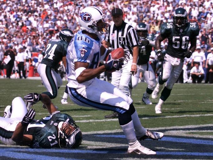 Tennessee Titans receiver Justin McCareins (86) pulls in a touchdown pass over Philadelphia Eagles defensive back Bobby Taylor (21) during their game at the Nashville Coliseum Sept. 8, 2002. The Titans won the season opener 27-24 over the Eagles.