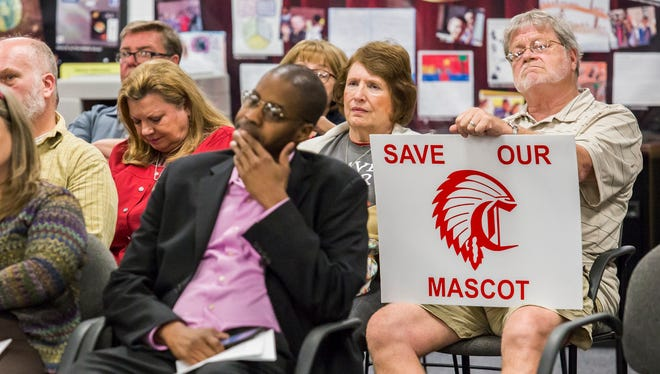 "Tim Laushey, a 1967 Conrad High School graduate and alumni band director, holds a sign reading ""Save Our Mascot,"" at a meeting over the use of the Redskins logo in Elsmere on Monday. A committee is suggesting to change the logo."