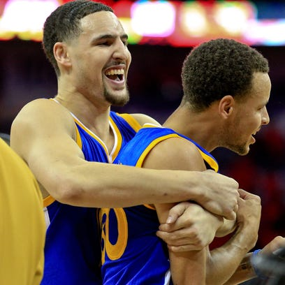 Warriors guard Stephen Curry, right,  celebrates with