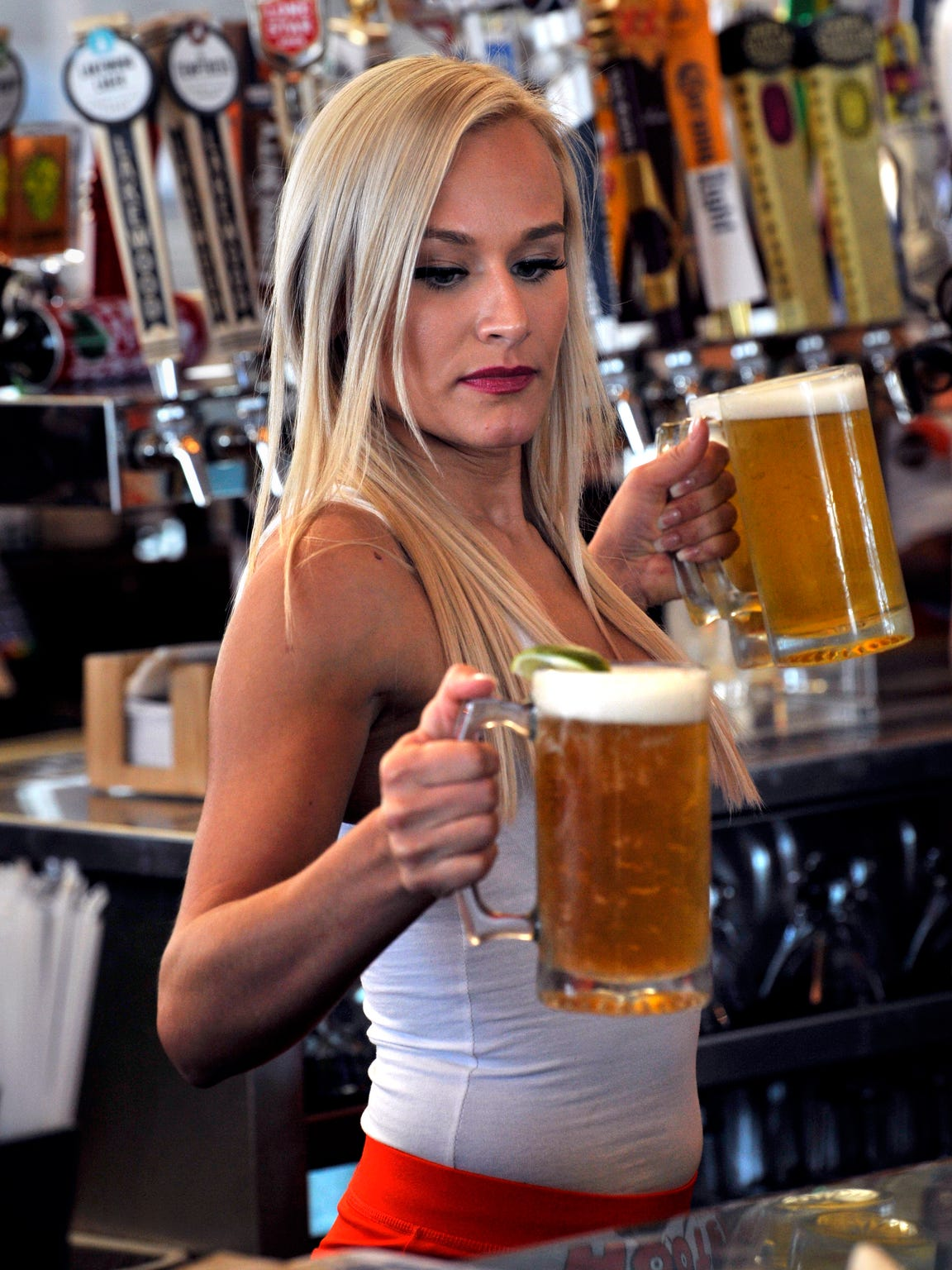 Allison Lyle, a bartender at Hooters, serves beer on the restaurant's opening day Jan. 16. Long thought never to open in Abilene, Hooters is located off Interstate 20 in northeast Abilene.
