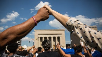 People hold hands during a rally lead by faith leaders in front of city hall calling for justice in response to the death of Freddie Gray on May 3 in Baltimore.