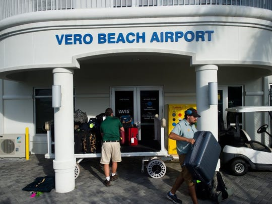 Norberto Montejano (right), of Vero Beach, who works as line service personnel at Vero Beach Regional Airport, unloads luggage for customers arriving on the Elite Airways flight from Newark Liberty International Airport on Thursday, March 17, 2016, in Vero Beach. (XAVIER MASCAREÑAS/TREASURE COAST NEWSPAPERS)