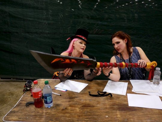 Costume judges Wendi Mitilinkas, left, and Amy Pass examine a sword from a costume contestant during the Marble City Comicon at the Knoxville Expo Center on April 23, 2016.