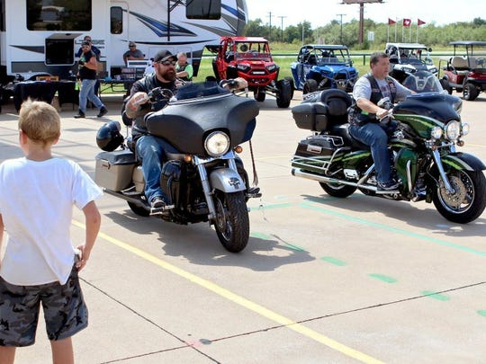 Mello (left) and Cameron 'Hitman' Goodwin compete in a slow race during the motorcycle rodeo at the Guardians for the Children Falls Town chapter's first Kruze for Kidz on Saturday afternoon at the Red River Harley Davidson.