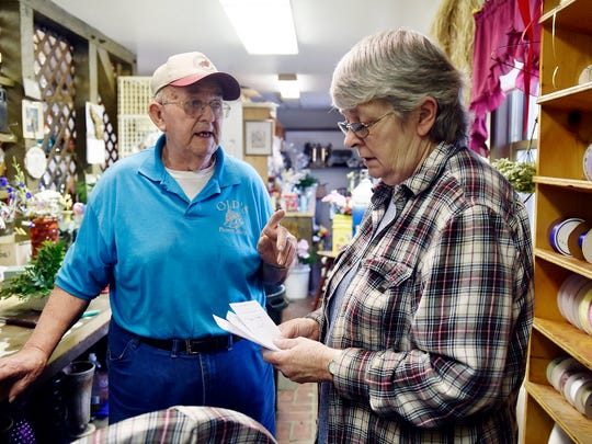Robert and Sue Olp review upcoming flower orders at Olp's Flower Shop in Jacobus.