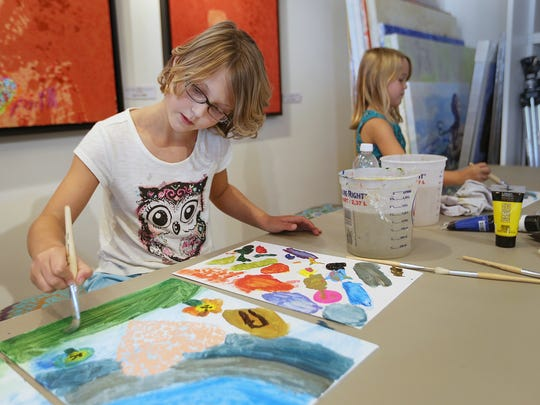 Leah Killinger, 9 (left), and Avery Harris, 8, paint at Walter Knabe's studio in south Broad Ripple. Knabe partnered with the Indiana Children's Wish Fund to paint with children who created and took home their own piece of art, and contributed to pieces to be auctioned off later.