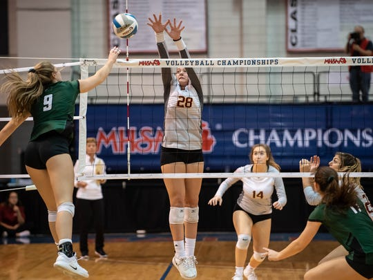 Farmington Hills Mercy's Julia Bishop (28) goes for the block against Lake Orion's Olivia Long (9) during MHSAA Volleyball semifinals at Kellogg Arena in Battle Creek.