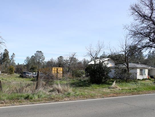 Shasta County sheriff's deputies and members of the bomb squad work to remove close to 100 pounds of explosives Tuesday in a barn behind this house off Happy Valley Road.