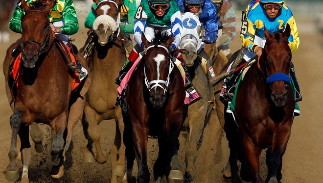 American Pharoah (5), far right, leads Materiality (8) and the rest of the field down the back stretch on the way to a Triple Crown victory during the 147th running of the Belmont Stakes horse race at Belmont Park, Saturday, June 6, 2015, in Elmont, N.Y. (AP Photo/Jason DeCrow)