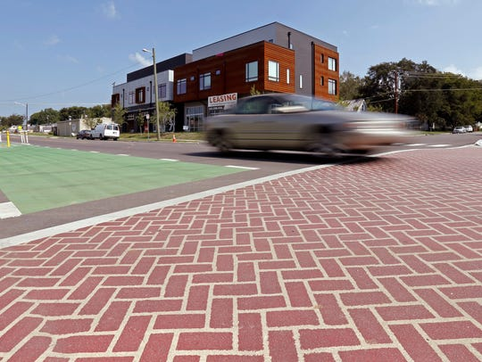A car passes over a new bricked crosswalk in the Nations