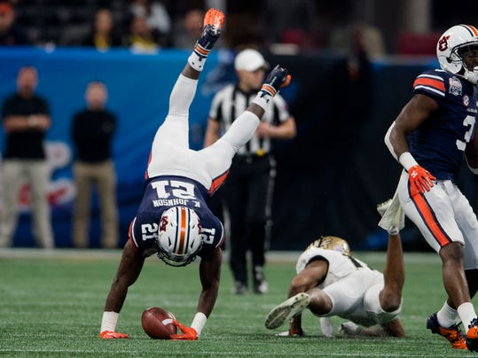 UCF defensive back Mike Hughes (19) tackles Auburn running back Kerryon Johnson (21) during the first half of the Peach Bowl NCAA college football game Monday, Jan. 1, 2018, in Atlanta, Ga. (Albert Cesare/The Montgomery Advertiser via AP)