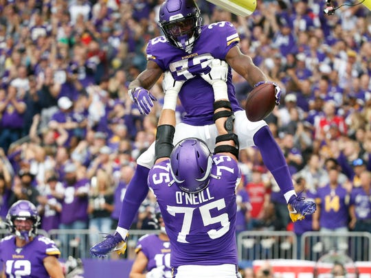 Minnesota Vikings running back Dalvin Cook (33) celebrates with teammate Brian O'Neill after a 19-yard touchdown run during the first half of an NFL football game against the Atlanta Falcons, Sunday, Sept. 8, 2019, in Minneapolis. (AP Photo/Bruce Kluckhohn)