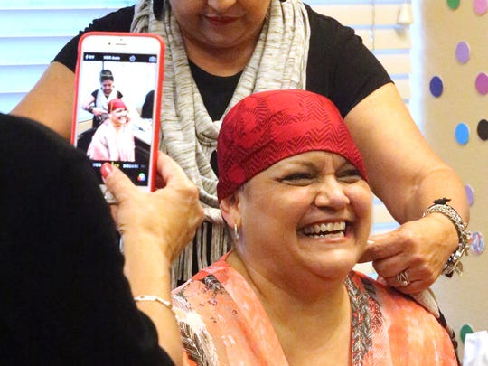 Cancer patient Patricia Ontiveros laughs while trying on a red scarf with help from Pat Martinez at the Rio Grande Cancer Foundation.