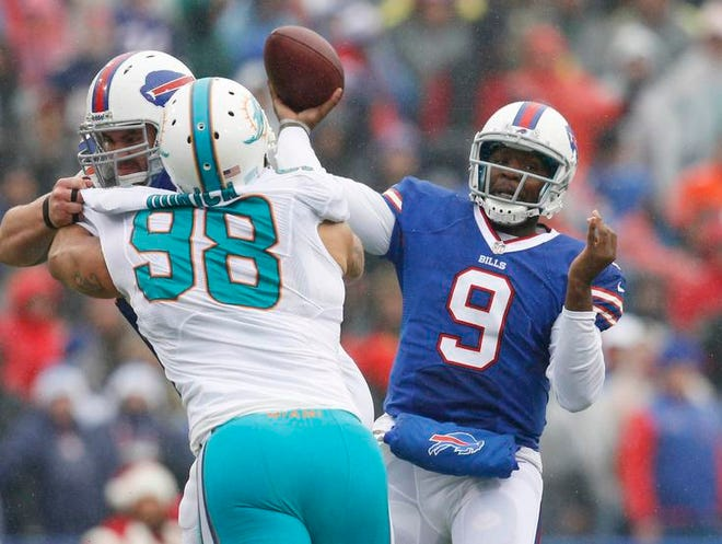 Buffalo Bills quarterback Thad Lewis (9) passes under pressure by Miami Dolphins defensive tackle Jared Odrick (98) during the first half at Ralph Wilson Stadium.