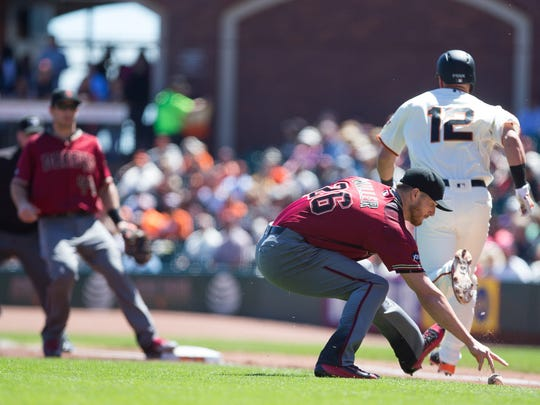 Arizona Diamondbacks starting pitcher Shelby Miller fields the ball behind San Francisco Giants second baseman Joe Panik as Panik runs safely to first base during the first inning at AT&T Park in San Francisco