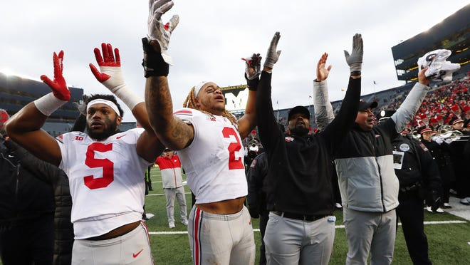 Ohio State's Baron Browning (5), Chase Young (2), linebackers coach Al Washington and head coach Ryan Day celebrate after a 56-27 win against Michigan in Ann Arbor, Mich., on Nov. 30, 2019.