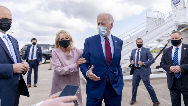 Jill Biden moves her husband, Democratic presidential candidate former Vice President Joe Biden, back from members of the media as he speaks outside his campaign plane at New Castle Airport in New Castle, Del., on Oct. 5, to travel to Miami for campaign events.
